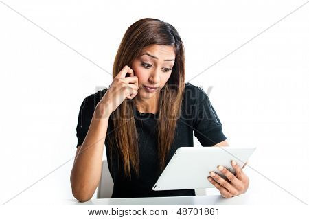 Attractive young Asian Indian teenage woman, working with a non-branded generic portable tablet looking concerned