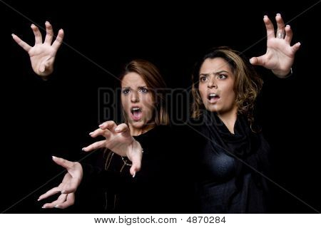 Portrait Of Surprised Young Women Showing Hand Gesture