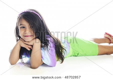 A beautiful young elementary girl looking at the viewer while laying on her belly in casual summer clothes.  On a white background.