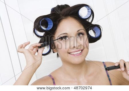 Closeup of a smiling young woman applying mascara