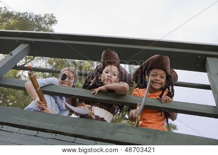 Low angle view of three kids in costumes looking through wooden railings