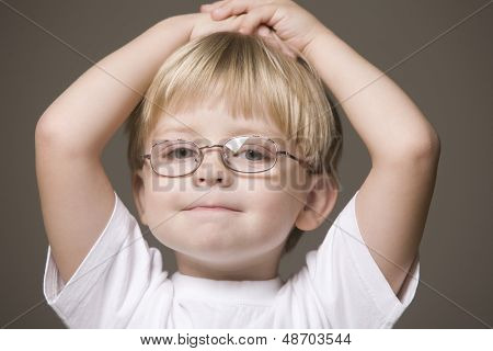Closeup portrait of a cute blonde haired boy wearing glasses against gray background