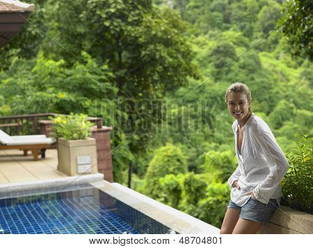 Portrait of a smiling young woman by swimming pool and against blurred trees