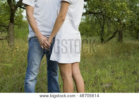 Side view midsection of young couple holding hands in orchard