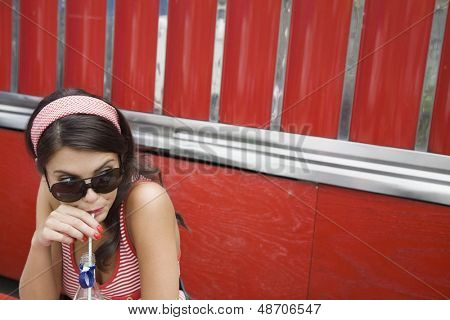 Closeup of a young woman in sunglasses drinking soda