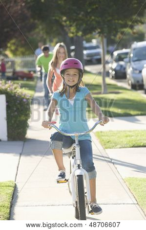 Portrait of a happy girl riding bicycle with blurred friends behind
