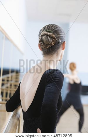 Rear view of young female ballet dancer standing by handrail in rehearsal room