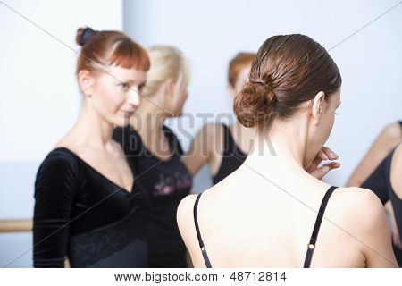 Rear view of woman with classmates standing in ballet rehearsal room
