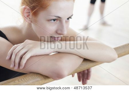 Beautiful young woman relaxing on ballet barre in rehearsal room
