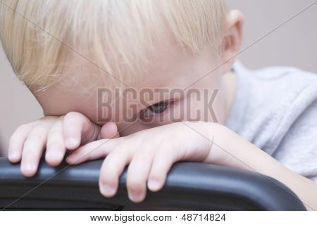 Closeup portrait of shy baby boy peeking over chair on colored background