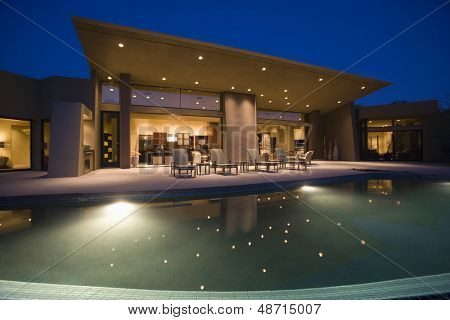 Luxurious and modern house with swimming pool at night