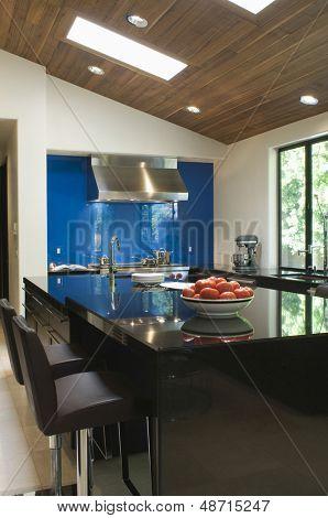 Blue backsplash and breakfast bar in modern kitchen