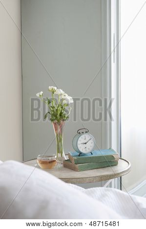 Bedside table with cut flower and alarm clock in bedroom