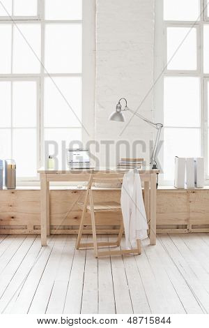 View of empty room with wooden table and chair in loft apartment