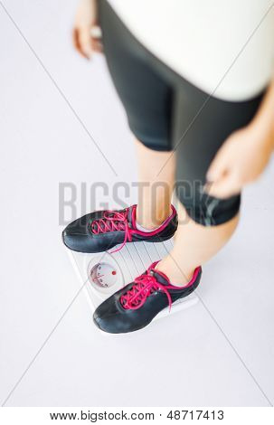 sport, diet and weight loss concept - woman legs standing on scales