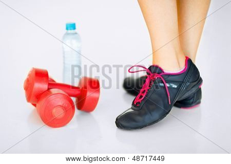 sport and recreation - sporty woman legs with light red dumbbells and water