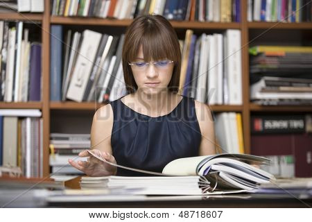 Young female designer going through documents in library