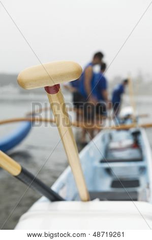 Wooden oar on outrigger canoe with canoeists in background at beach