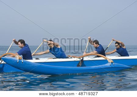 Side view of male rowers paddling outrigger canoe in race