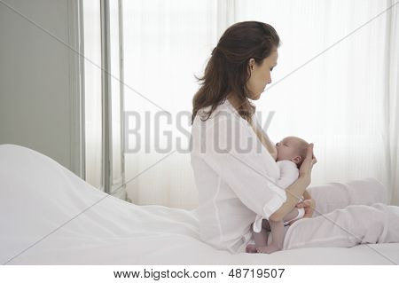 Mother breastfeeding newborn baby in bedroom