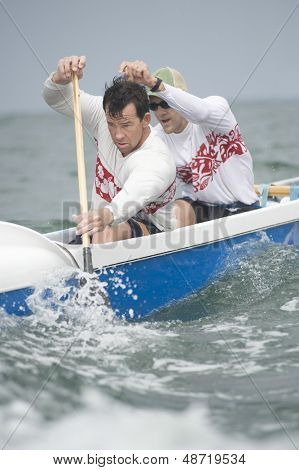 Confident male rowers paddling outrigger canoe in race