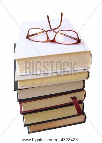 Books pile with glasses on top, isolated in white