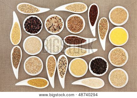 Large grain and cereal food selection in white porcelain bowls over hessian background.