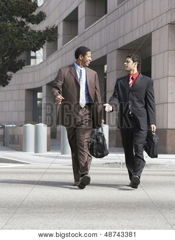 Two multiethnic business men walking on city street against buildings