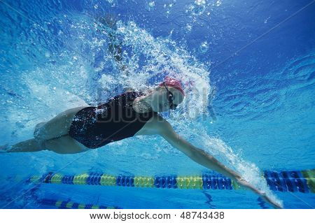 Low angle view of a young woman swimming underwater
