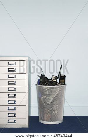 Mobile phones in trash can by filing cabinet