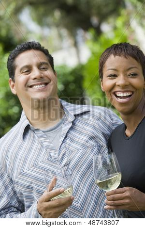 Cheerful multiethnic couple with wine glasses outdoors