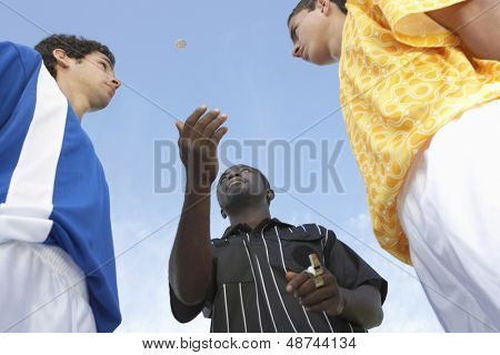 Low angle view of referee flipping a coin before the football game