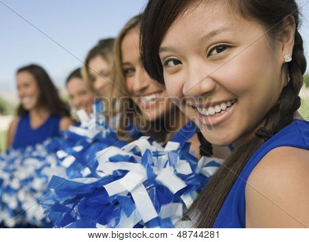 Blurred cheerleaders in a row with focus on girl in foreground
