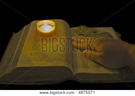 Male Hand Lies On Ancient Bible With A Big Christian Cross In The Light Of A Candle Over Black Backg