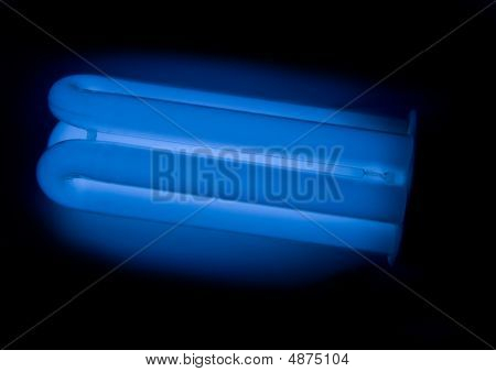 Energy Saving Lamp (lightbulb) With Dark Blue Colour On The Black Background