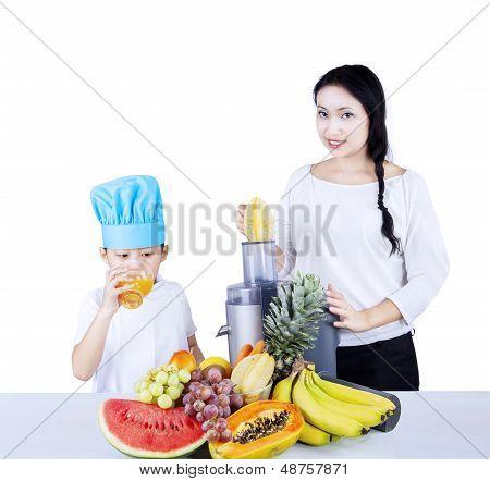 Woman Making Fruit Juice To A Boy