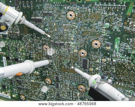 Multimeter Probes Examining A Circuit Board