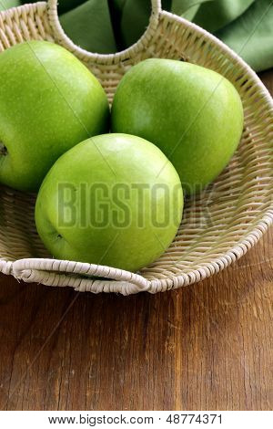 "green apples ""Granny Smith"" in a basket on the table"