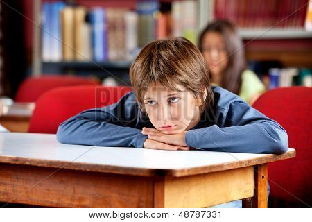 Bored little schoolboy looking away while leaning on table in library with female classmate in background