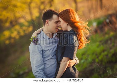 couple kissing standing outdoos among bushes
