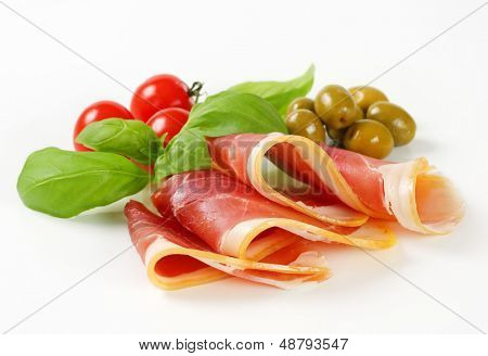 thin slices of prosciutto with tomatoes, basil and olives