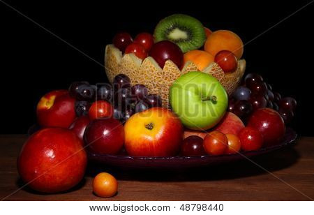 Assortment of juicy fruits on wooden table, on  dark background