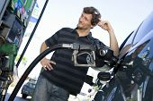Blurred smiling man refueling car at the natural gas station