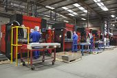 stock photo of manufacturing  - Rear view of workers at manufacture workshop operating machines - JPG