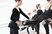 stock photo of ballerina  - Ballet teacher adjusting foot positions of ballerinas at the barre - JPG