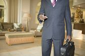Midsection of businessman with cell phone and briefcase in hotel lobby