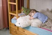 foto of bunk-bed  - Thoughtful young boy with polar bear soft toy lying on bunk bed - JPG