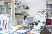 image of untidiness  - Side view of businessman using landline phone in creative office space - JPG