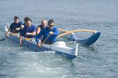 picture of canoe boat man  - Male rowers paddling outrigger canoe in race - JPG