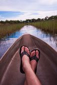 picture of canoe boat man  - mans feet relaxing a canoe with an interesting point of view - JPG